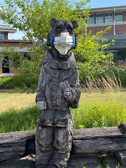 """Mishka wears a mask made from a cotton Coralville Library book bag. Mishka is sculpture who was donated by the artist Valery Kovalev and installed on the front lawn. Citation: Alexander, Ellen - Library Assistant Director. (2020, July 14). """"Mishka wearing a mask."""" Coralville Digital History Library. Retrieved from https://coralvilledigitalhistory.omeka.net/items/show/351"""